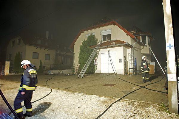 Tűzoltók dolgoznak 2015. november 7-én este a pilisjászfalui Cséri úton, ahol kigyulladt és teljes terjedelmében égett egy családi ház ötszáz négyzetméteres tetőszerkezete. A családi házból a bent tartózkodók kimenekültek, egy 15 év körüli lányt füstmérgezés gyanújával kórházba vittek. MTI Fotó: Lakatos Péter