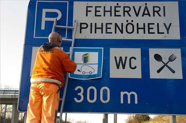 Elektromosautó-töltőállomást előjelző táblát helyeznek ki az M7-es autópálya 57-es kilométerszelvényében, Székesfehérvár közelében, a fehérvári pihenő előtt 2016. december 3-án. MTI Fotó: Lakatos Péter