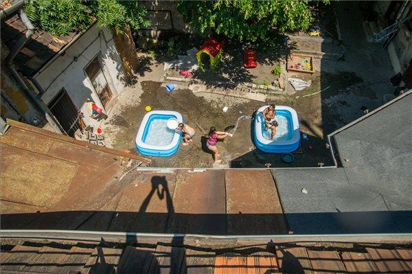 Gyerekek hűsölnek medencékben a kánikulában egy belvárosi bérház udvarán Budapesten, a nyolcadik kerületben 2017. augusztus 1-jén. Erre a napra az Országos Meteorológiai Szolgálat az összes megyére első-, másod- és harmadfokú figyelmeztetéseket adott ki a hőség miatt, két megyében - Csongrád és Békés - van érvényben a legmagasabb, harmadfokú (piros) figyelmeztetés. MTI Fotó: Balogh Zoltán