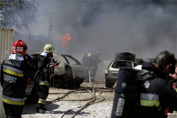 Egy autószerelő-műhelyben keletkezett tűz oltásán dolgoznak tűzoltók a fővárosi Soroksári úton 2015. július 22-én. A tűzben nem sérült meg senki. Az oltás idejére a H6-os HÉV helyett pótlóbusz járt az érintett szakaszon. MTI Fotó: Mihádák Zoltán