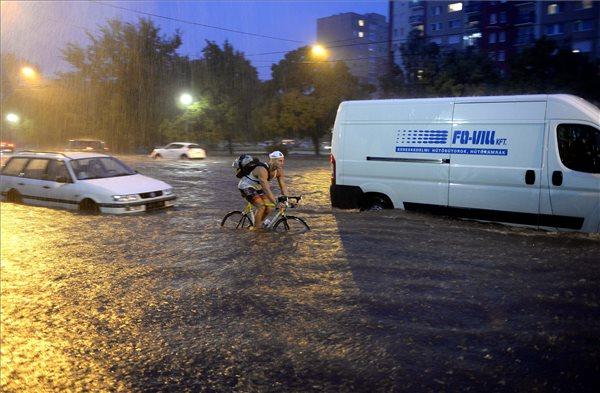 Budapest, 2015. augusztus 17. Egy kerékpáros közlekedik a vízzel elöntött XIII. kerületi Béke térnél 2015. augusztus 17-én. Egy óra alatt több eső esett a főváros belső részén, mint az augusztusi havi átlag. MTI Fotó: Bruzák Noémi