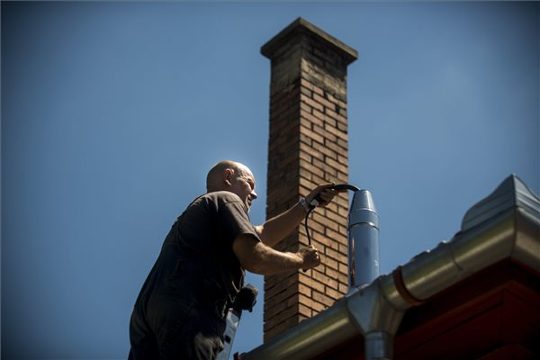 A Fővárosi Kéményseprőipari Kft. (FŐKÉTÜSZ) kéményseprője egy csepeli ház tetején a kondenzációs gázkazán égéstermék-elvezető csövét ellenőrzi a Határ utcában 2016. július 4-én. A kötelező kéményellenőrzés és -tisztítás július 1-jétől ingyenes és magáncégek helyett az Országos Katasztrófavédelmi Főigazgatósághoz (OKF) került. Korábban a kéményseprés már olyan drága volt, hogy sokakat ez riasztott el a rendszeres ellenőrzés megrendelésétől. MTI Fotó: Marjai János