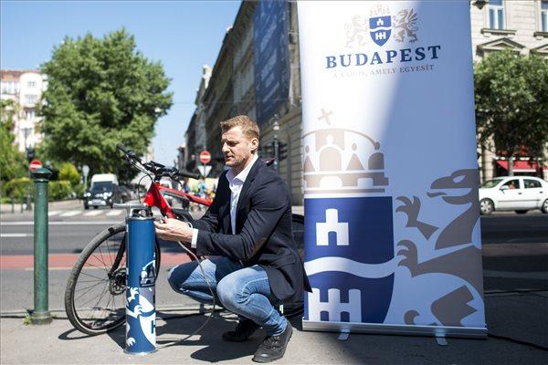 Kadlecsek Krisztián, a tv2 Aktív című műsorának vezetője egy ingyenes kerékpárpumpa mellett. MTI Fotó: Marjai János